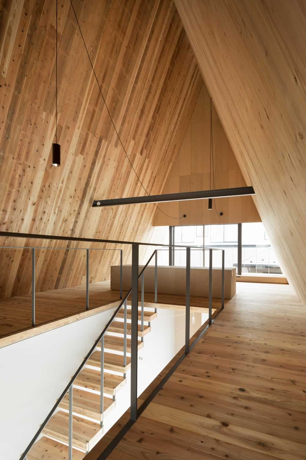 This is a close look at the second level of the house with a tall wooden shiplap cathedral ceiling that matches the flooring.