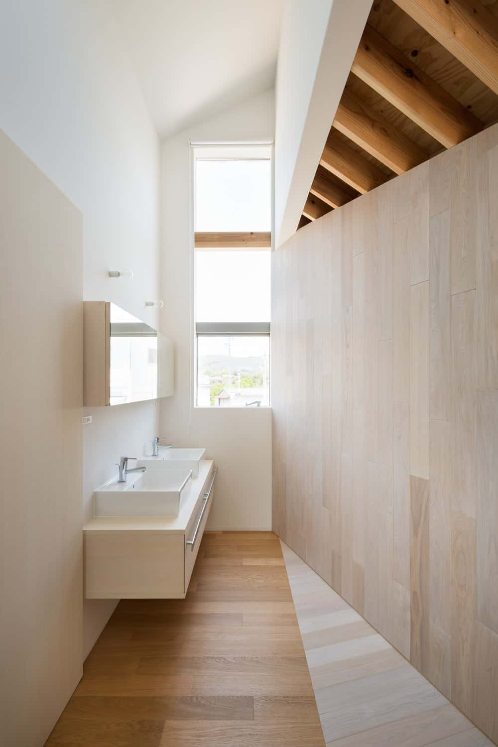 This is the bathroom with a two-sink floating vanity with a beige tone that lets it blend with the wall.