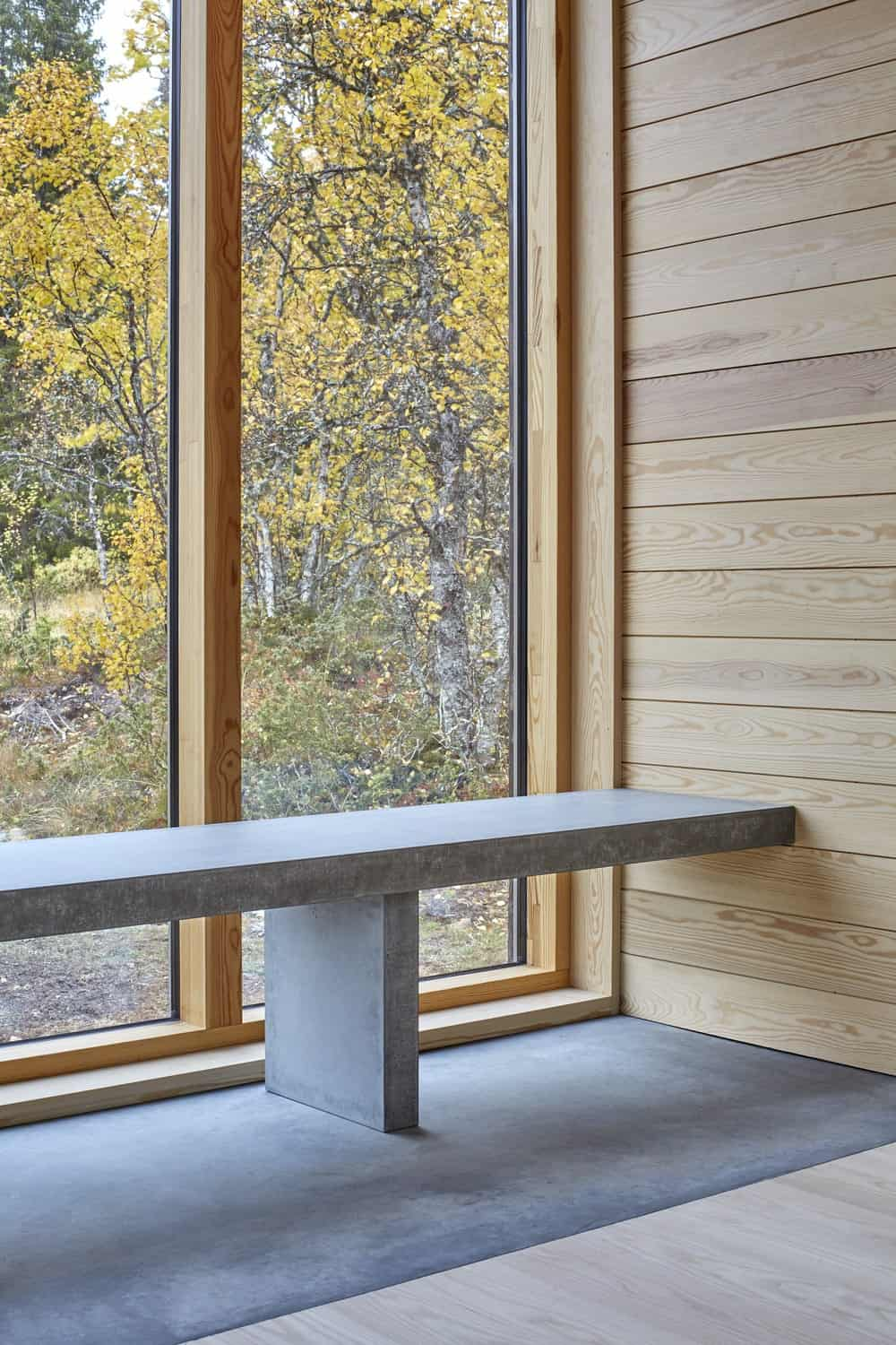 This corner of the house has a built-in stone bench that pairs well with the flooring and gives a nice complement to the glass wall and wooden wall.