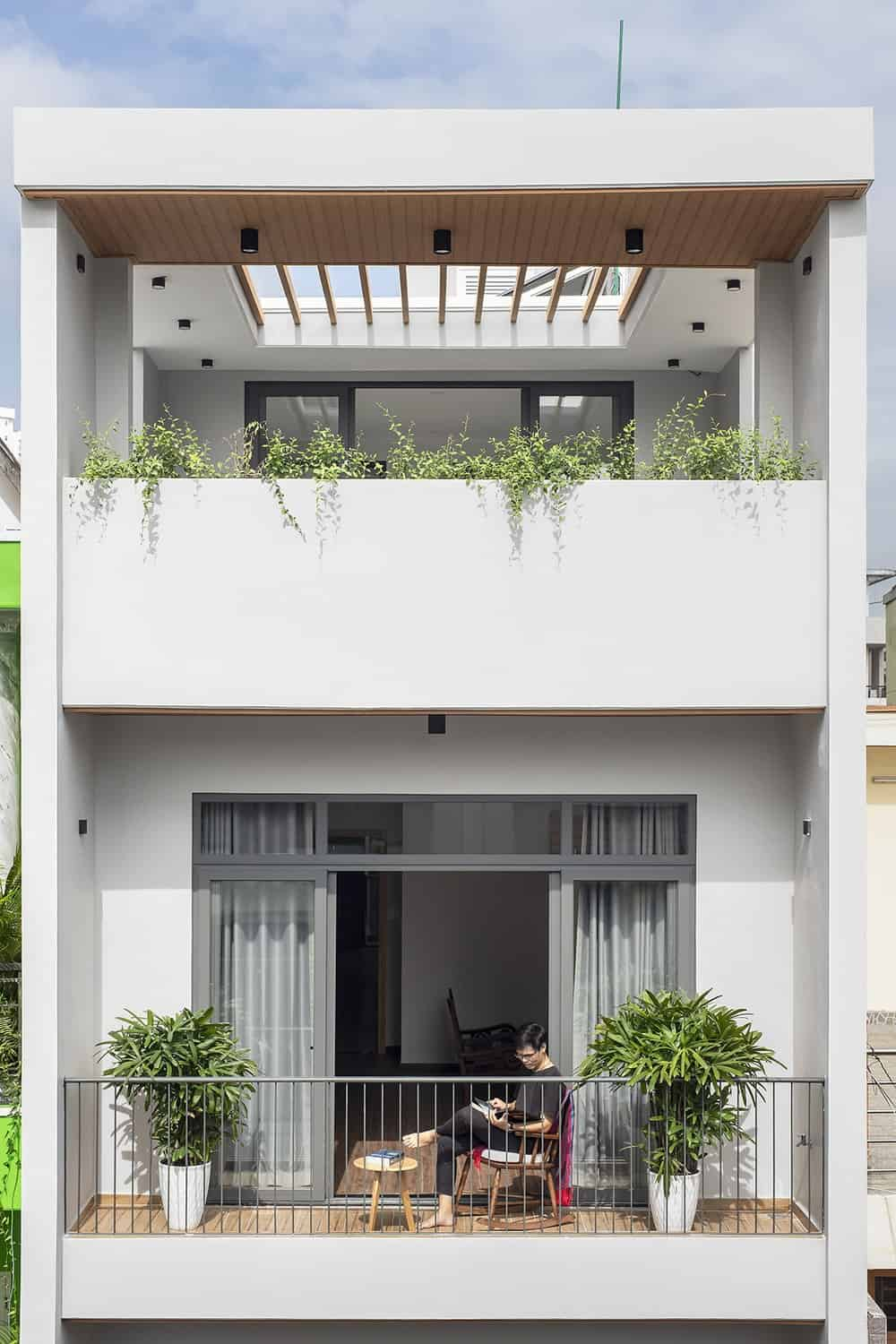 This is a close look at the third floor and rooftop balconies adorned with planters and potted plants that bring color to the concrete exterior walls.