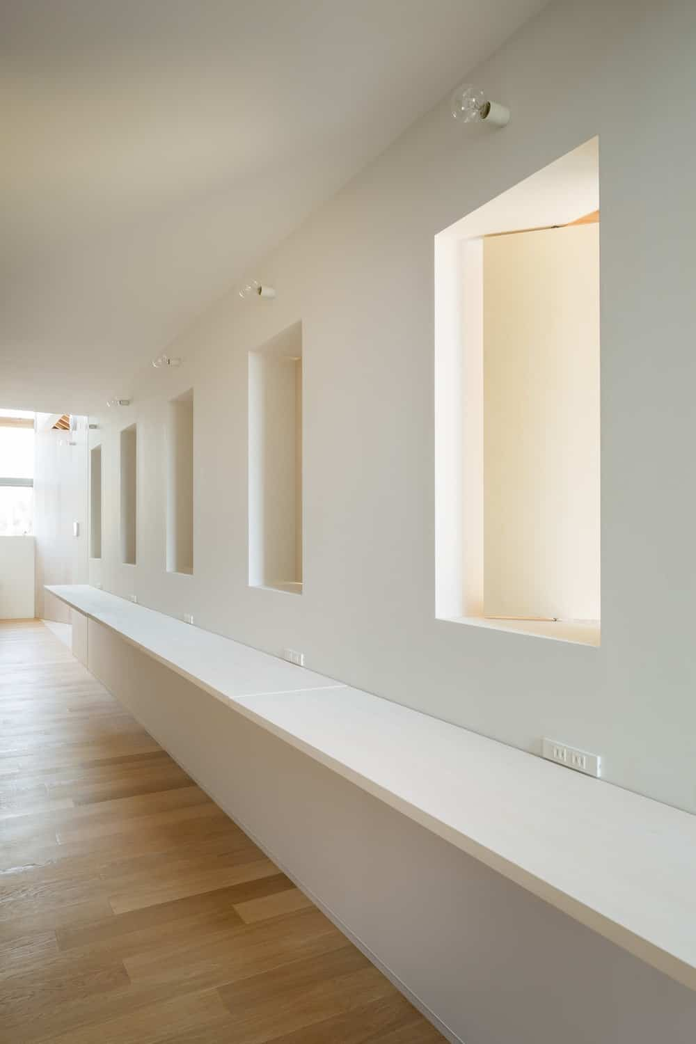 This side of the house has a long floating shelf belong a row of windows that can fit mirrors for a spacious salon. This area has a consistent beige tone illuminated by natural lights.