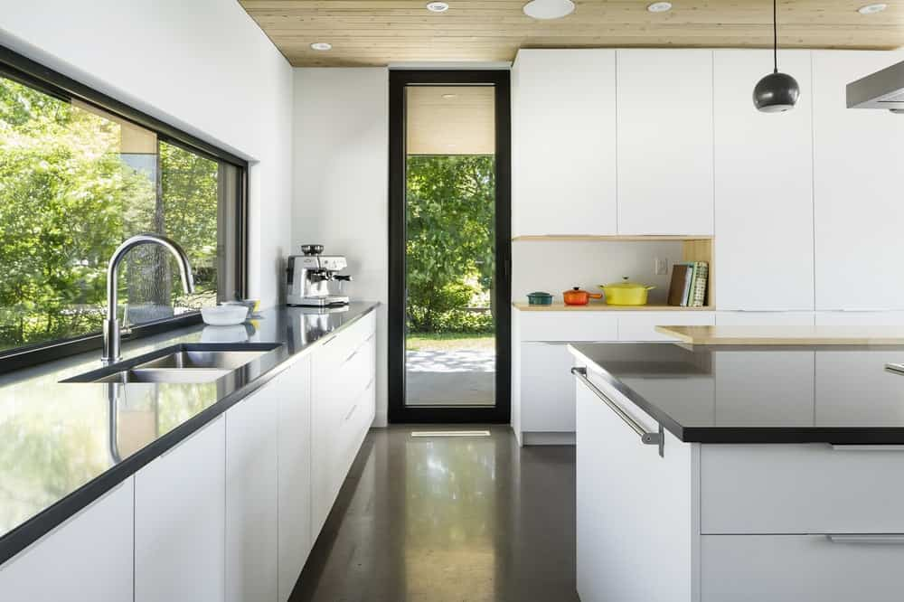 There is a glass back door exit at the far corner of the kitchen cabinetry that are contrasted by the black countertops.