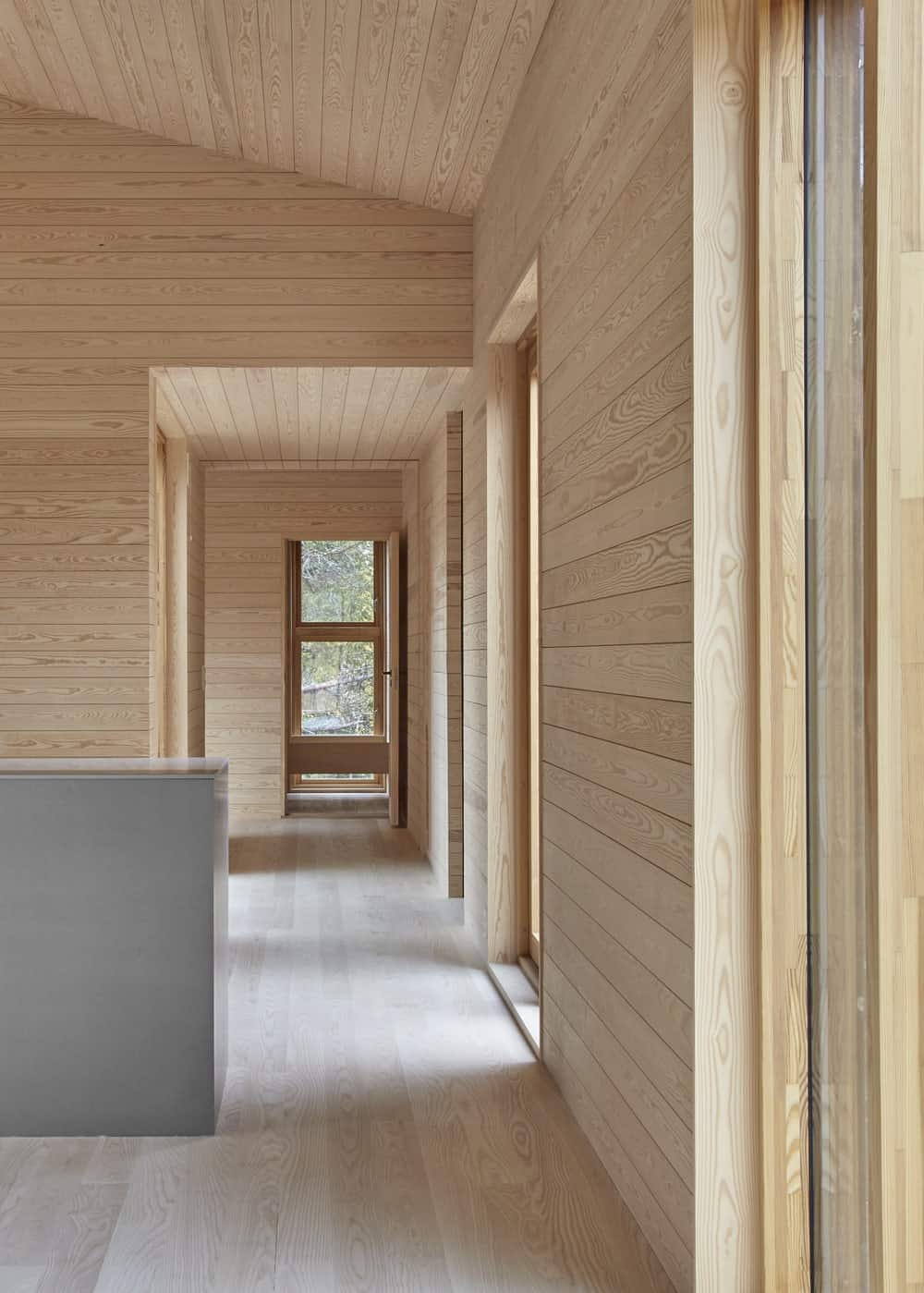 This is a look at the hallway of the house that has consistent light wooden shiplap walls and tall arched ceiling.
