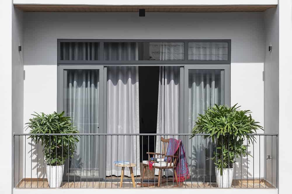 This is balcony has a wooden flooring, a couple of potted plants on opposite ends and a wooden chair.