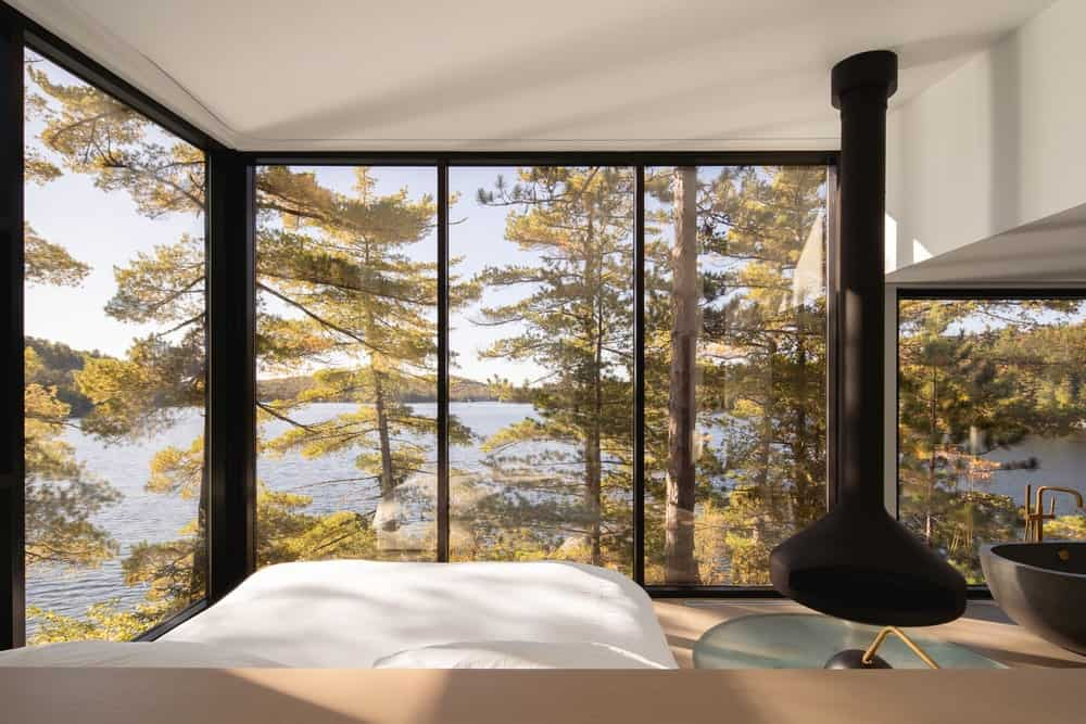 This is the bedroom with a platform bed surrounded by glass walls giving it a unique view of the lake and trees.