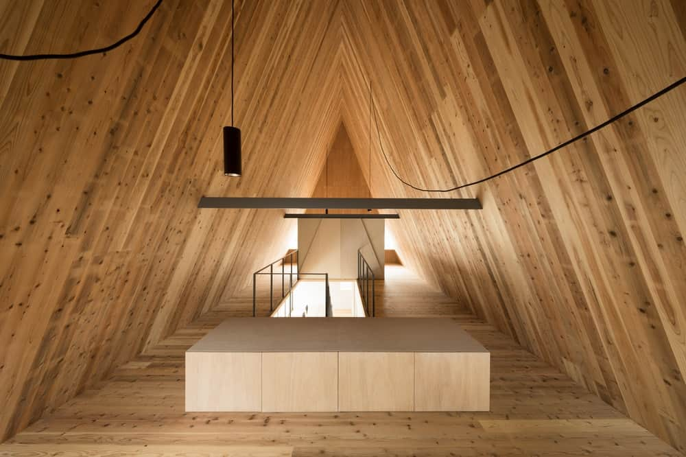 The wooden shiplap cathedral ceiling is supported by a couple of exposed wooden beams and makes the wiring of the pendant lights stand out.