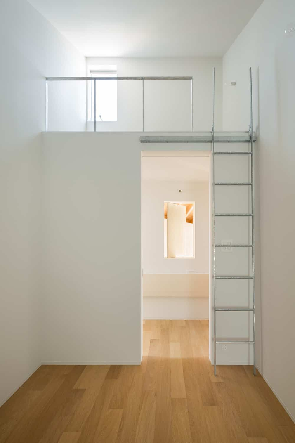 This bedroom has a space above the entryway for the bed that is accessed with a ladder to save space and maximize the vertical area.