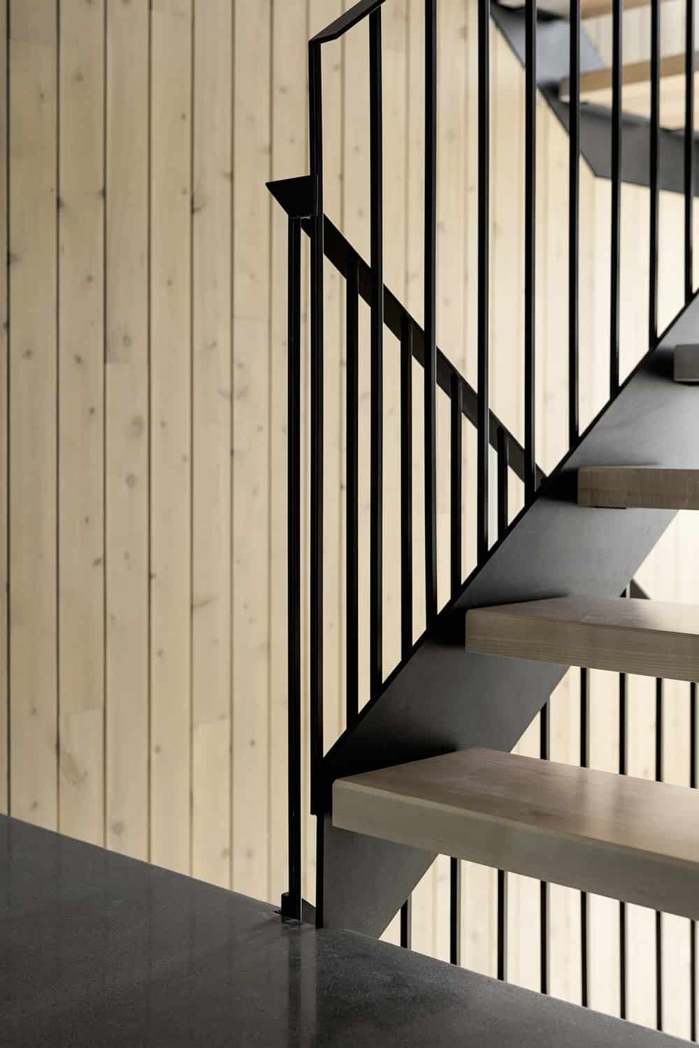 This is a close look at the staircase that has light wooden steps that contrast with the black wrough iron railings and banisters.