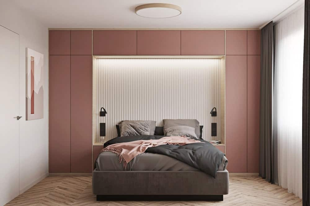 This other bedroom has an earthy rose paneled wall that serves as a headboard for the large bed with a built-in alcove that has a modern lighting.