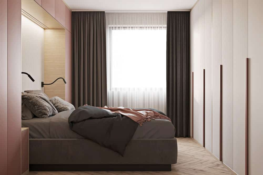 The bedroom is illuminated by the window on the far side with light-out dark gray curtains that match the tone of the bed sheets.