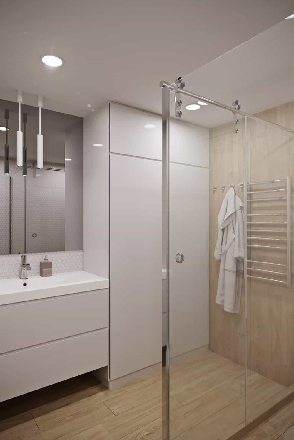 This is the view of the bathroom from the vantage of the toilet showcasing more of the glass enclosed shower area and the bright beige floating vanity with modern cabinetry.