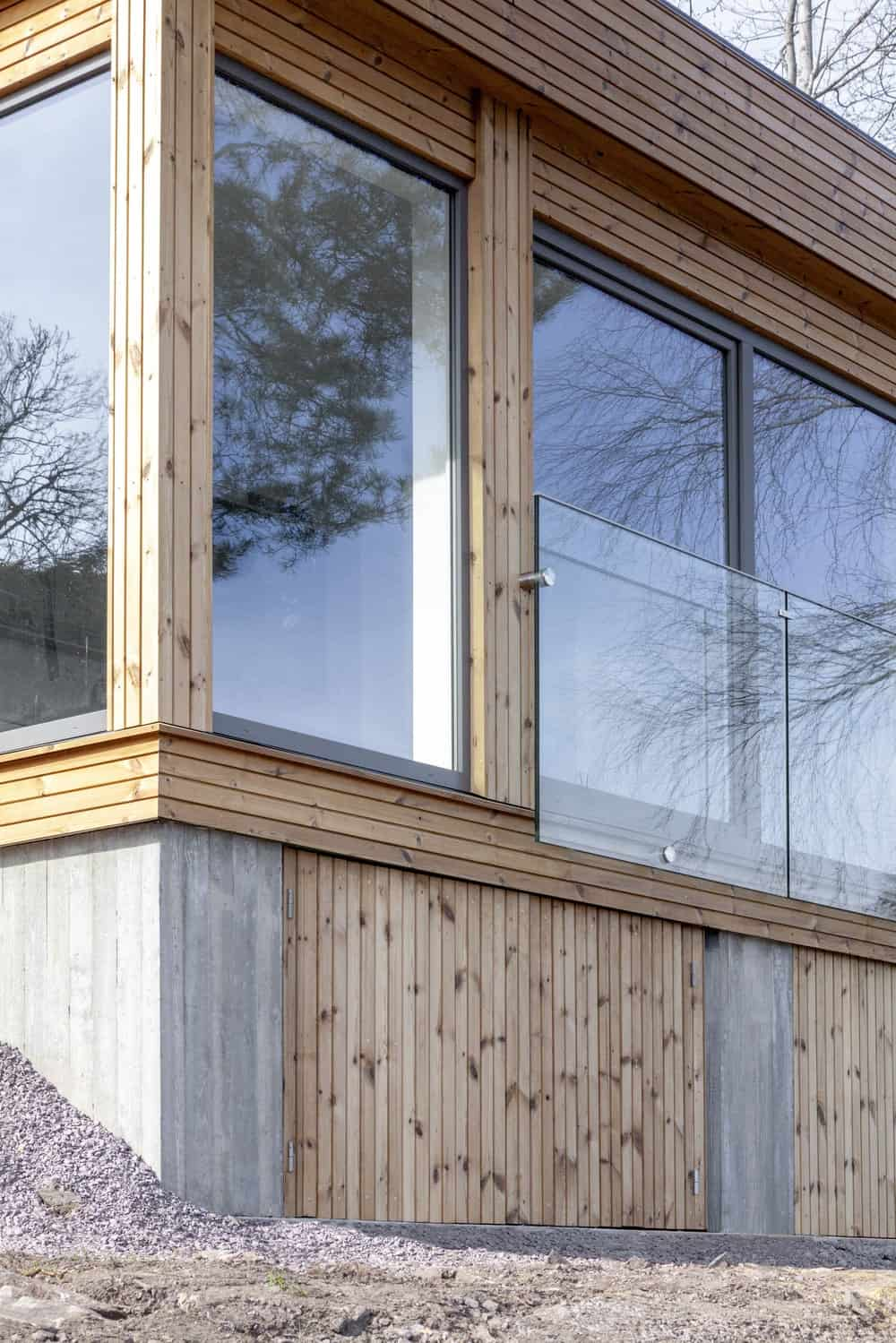 This is a close look at the exterior of the house with wooden shiplap elements, concrete elements and large glass walls and windows as well as railings.