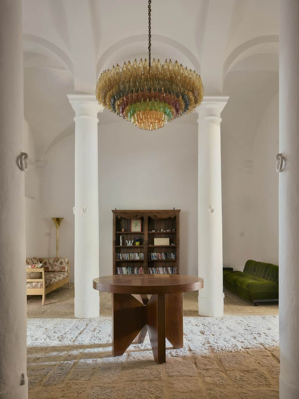 Upon entry of the house, you are welcomed by this foyer with a round wooden table, greek pillars and a decorative lighting above.