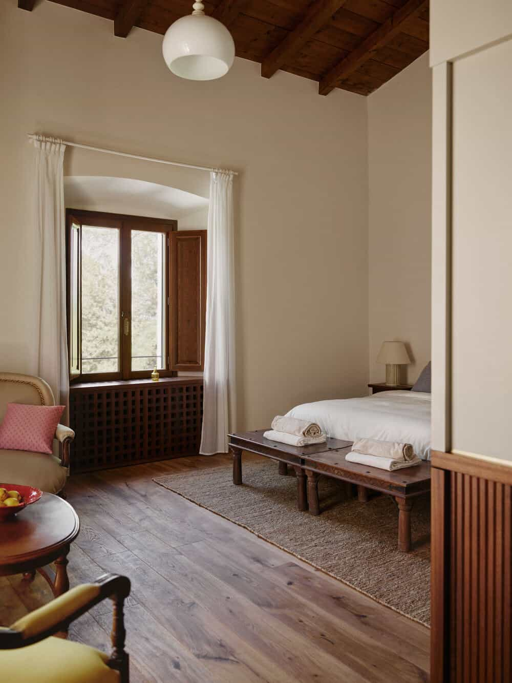 This view of the bedroom showcases the wooden bench at the foot of the bed and the window with a build-in bench on the far side.