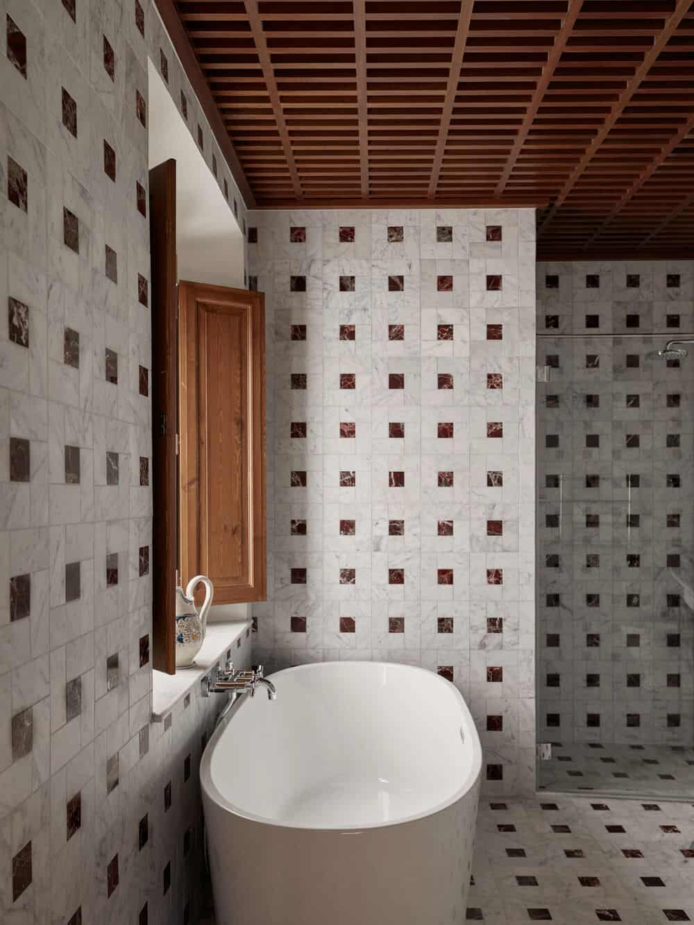 This is a closer look at the bathroom that has a freestanding bathtub that stands out against the patterned walls by the window.