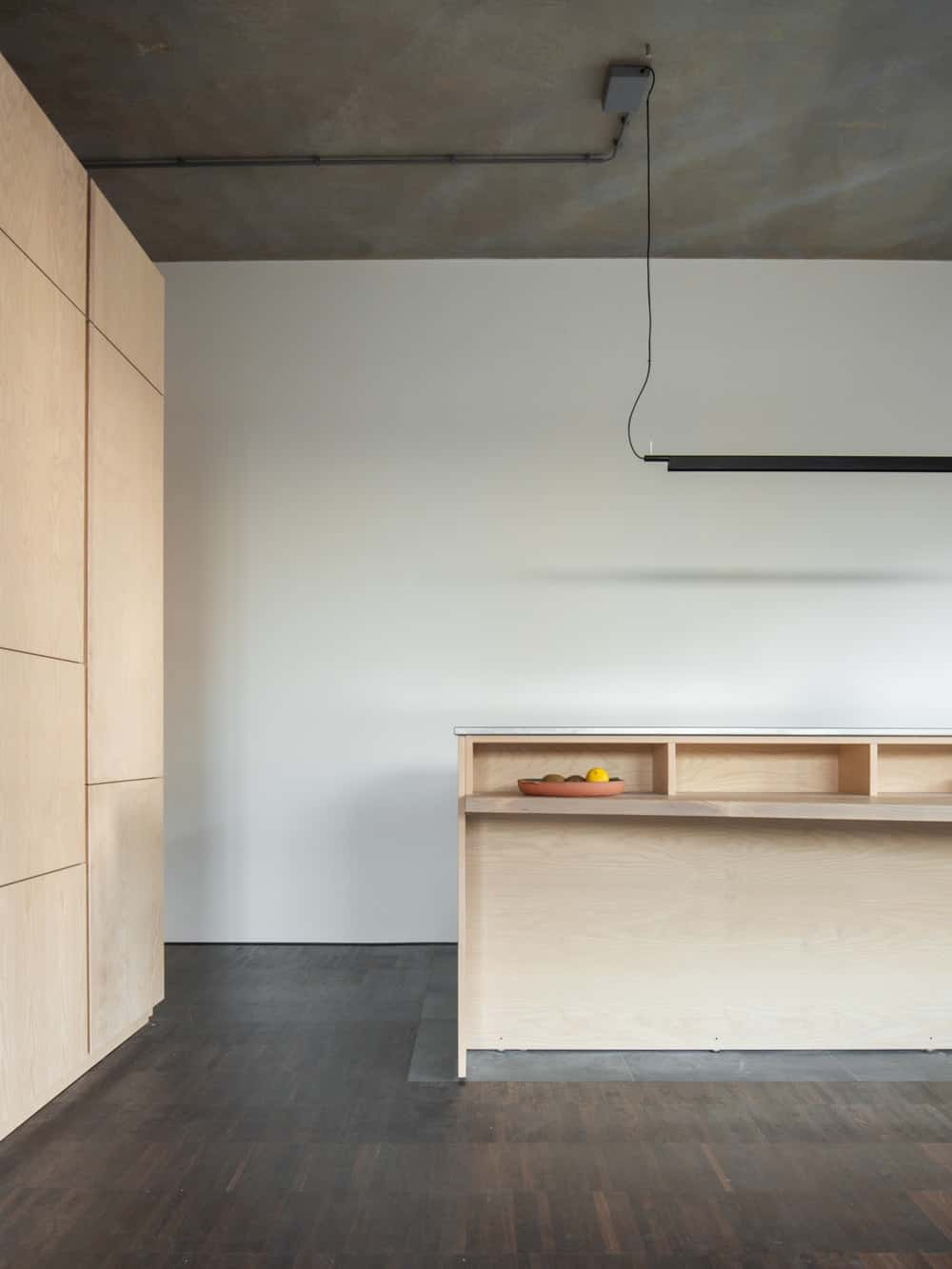 The kitchen island is topped with a modern and sleek black lighting that hangs from the concrete gray ceiling.