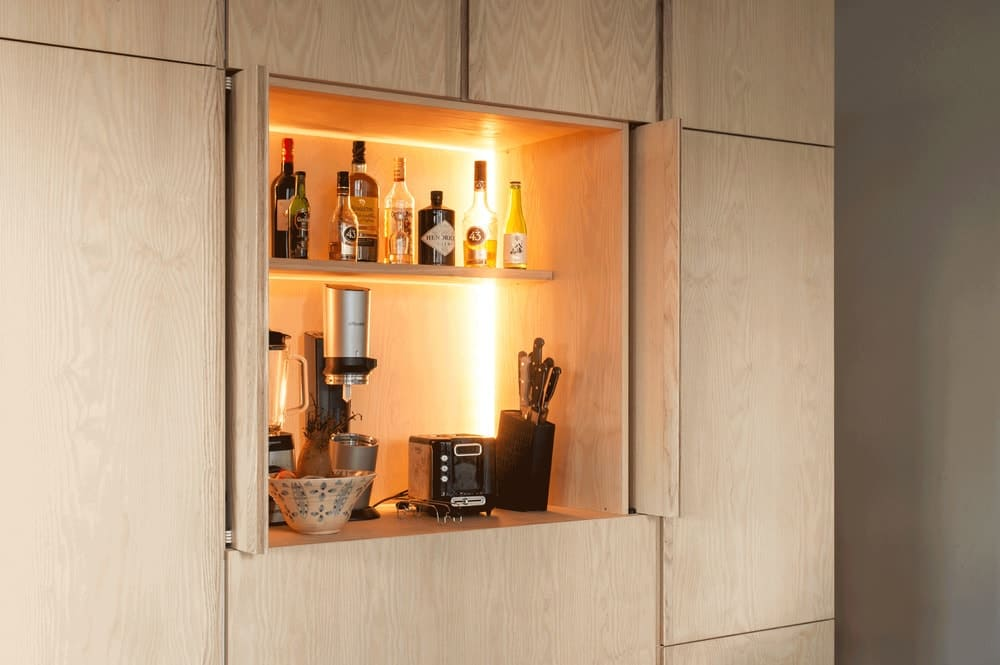 This is a close look at the wooden cabinet of the kitchen that opens up to reveal the small appliances inside with its own lighting.