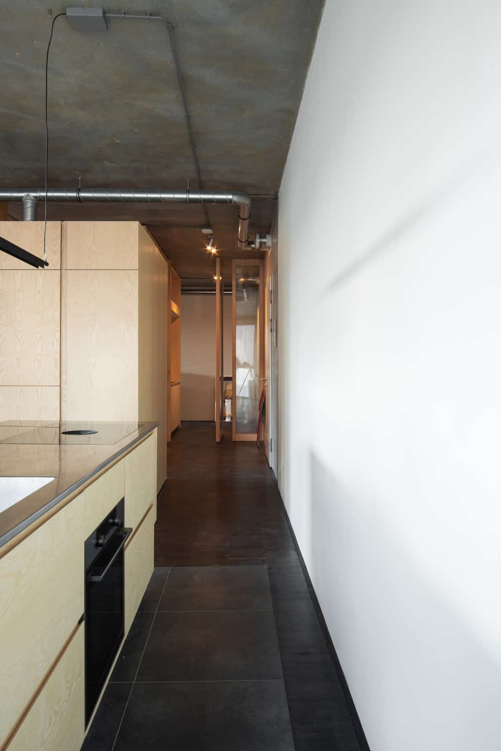 This is a look at the side of the kitchen cabinetry that leads to the pantry and shows more if the industrial-style feel of the ceiling with its exposed pipes.