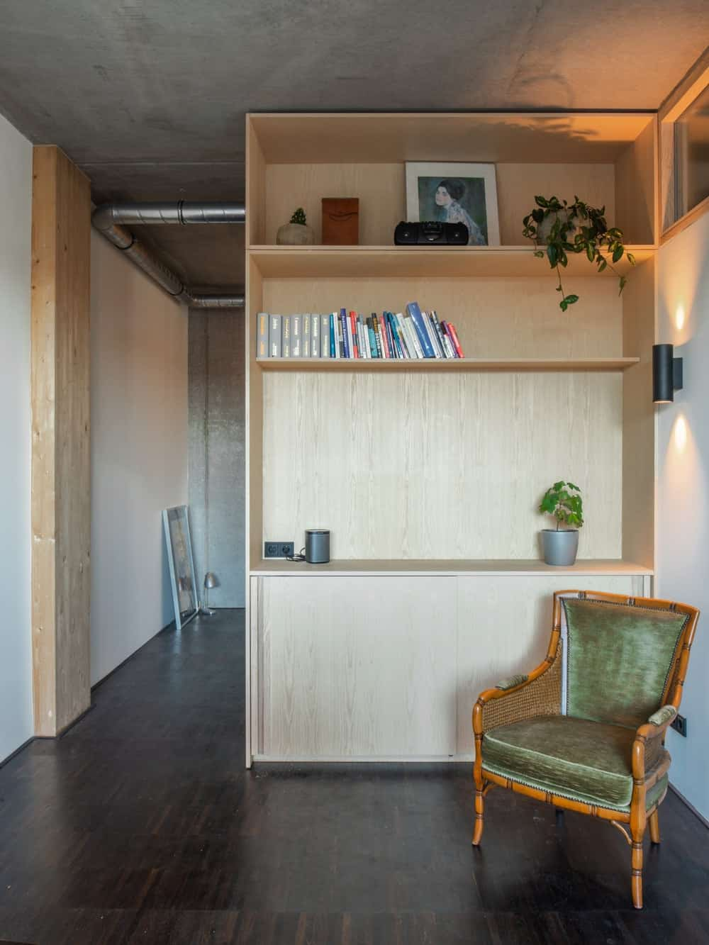 This is a library corner of the house with a comfortable armchair that is perfect as a reading nook by the wooden bookshelves.