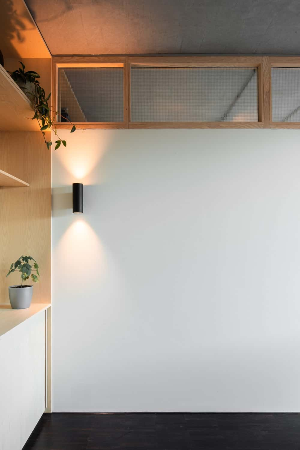 This area is lit with wall-mounted sconce that throws warm lighting downward and upward.