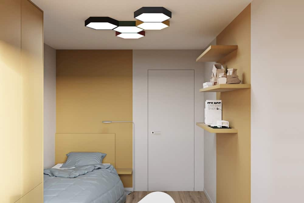 This bedroom has a modern set of flush-mount ceiling lights above a gray cottage-style bed.