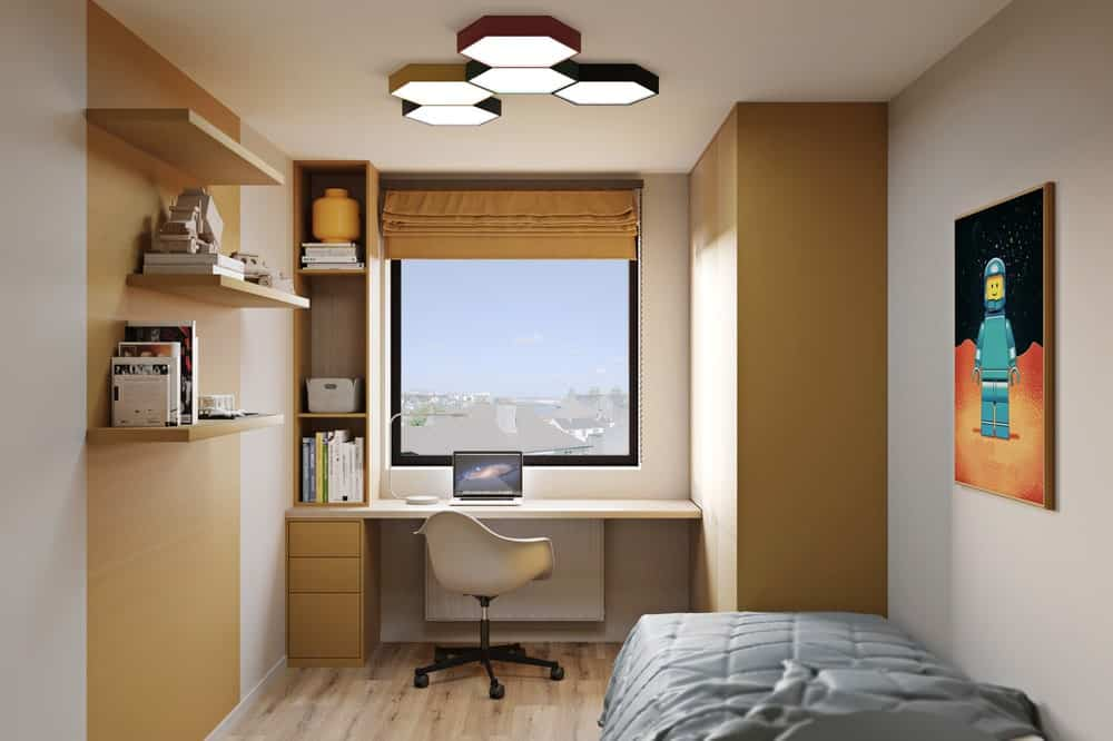 Across from the bed is a study area with a built-in wooden desk, drawers and shelves brightened by the large window.