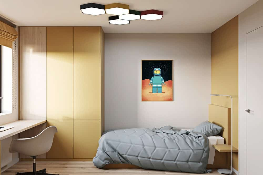 This is another view of the whole bedroom with a gray bed, wooden built-in structures and a colorful wall-mounted artwork for a dash of color.
