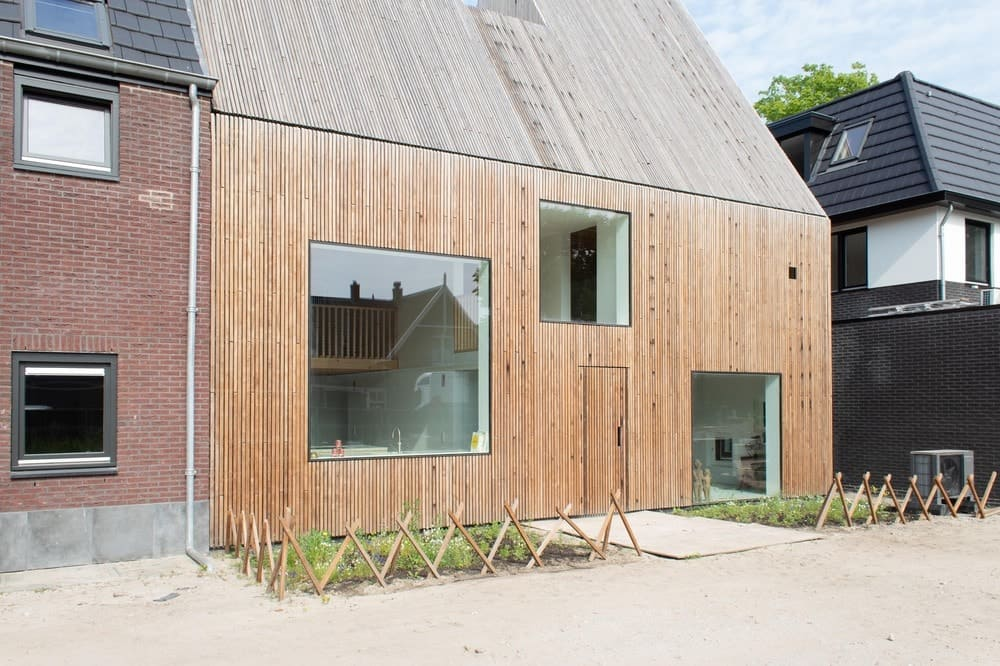This is a closer look at the front of the house showcasing the large square glass windows that bring in natural lighting.