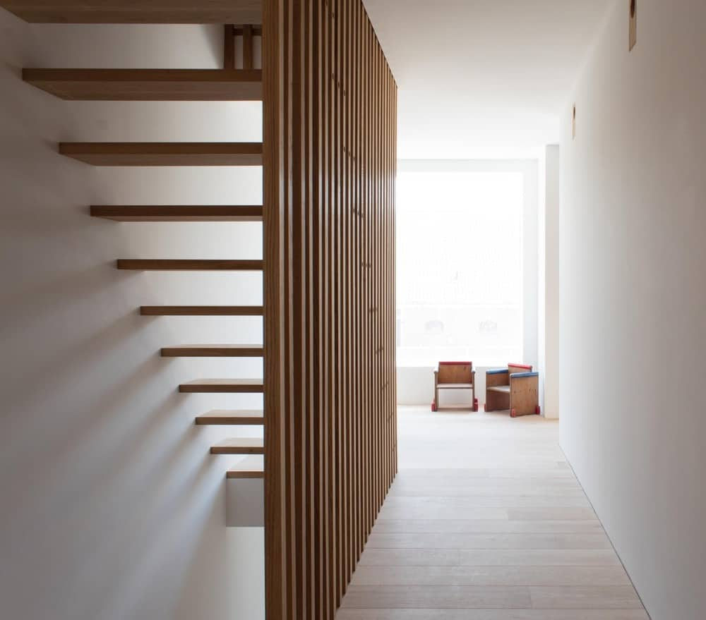 This is the second-floor landing with a wooden staircase that stands out against the bright elements illuminated by the window on the far side.