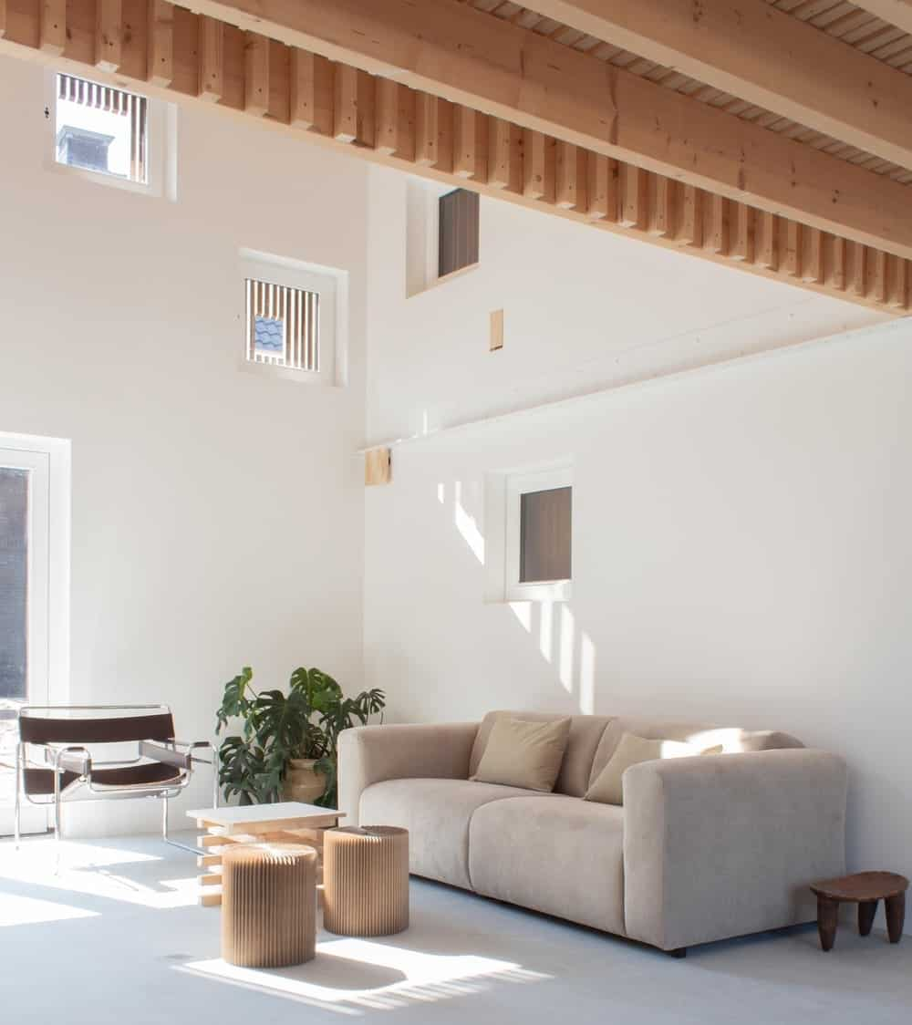The bright and airy living room has a tall ceiling, light gray sofa and stools that match the wooden ceiling.