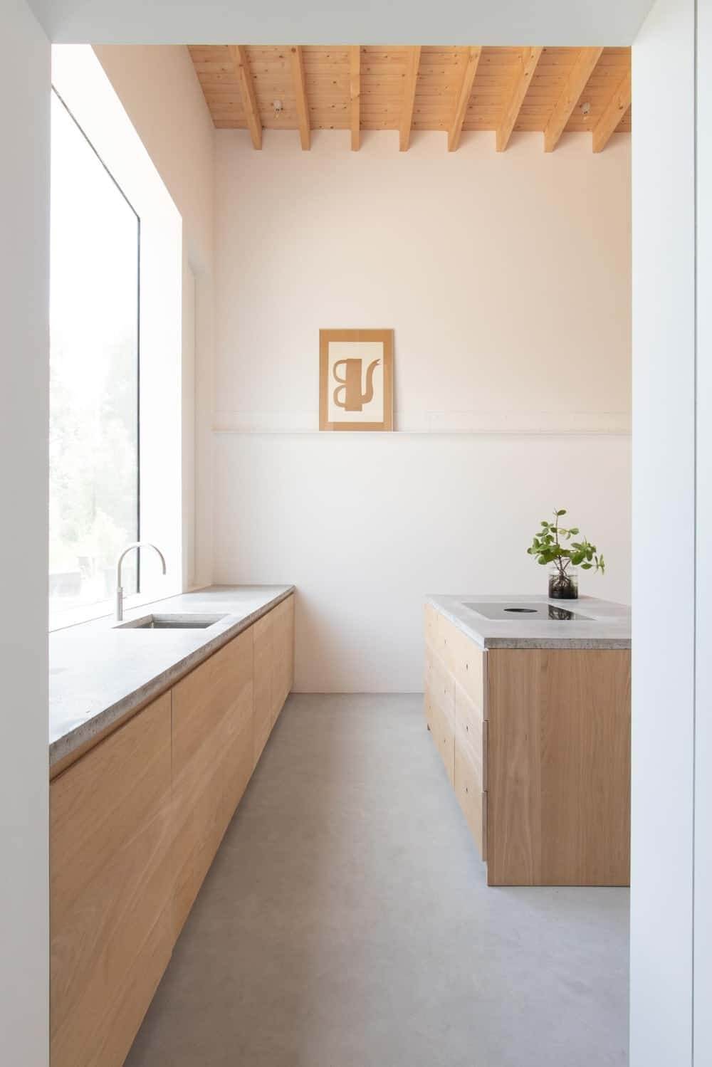 The kitchen has a tall wooden beamed ceiling that matches the tone of the wooden cabinetry of the kitchen.