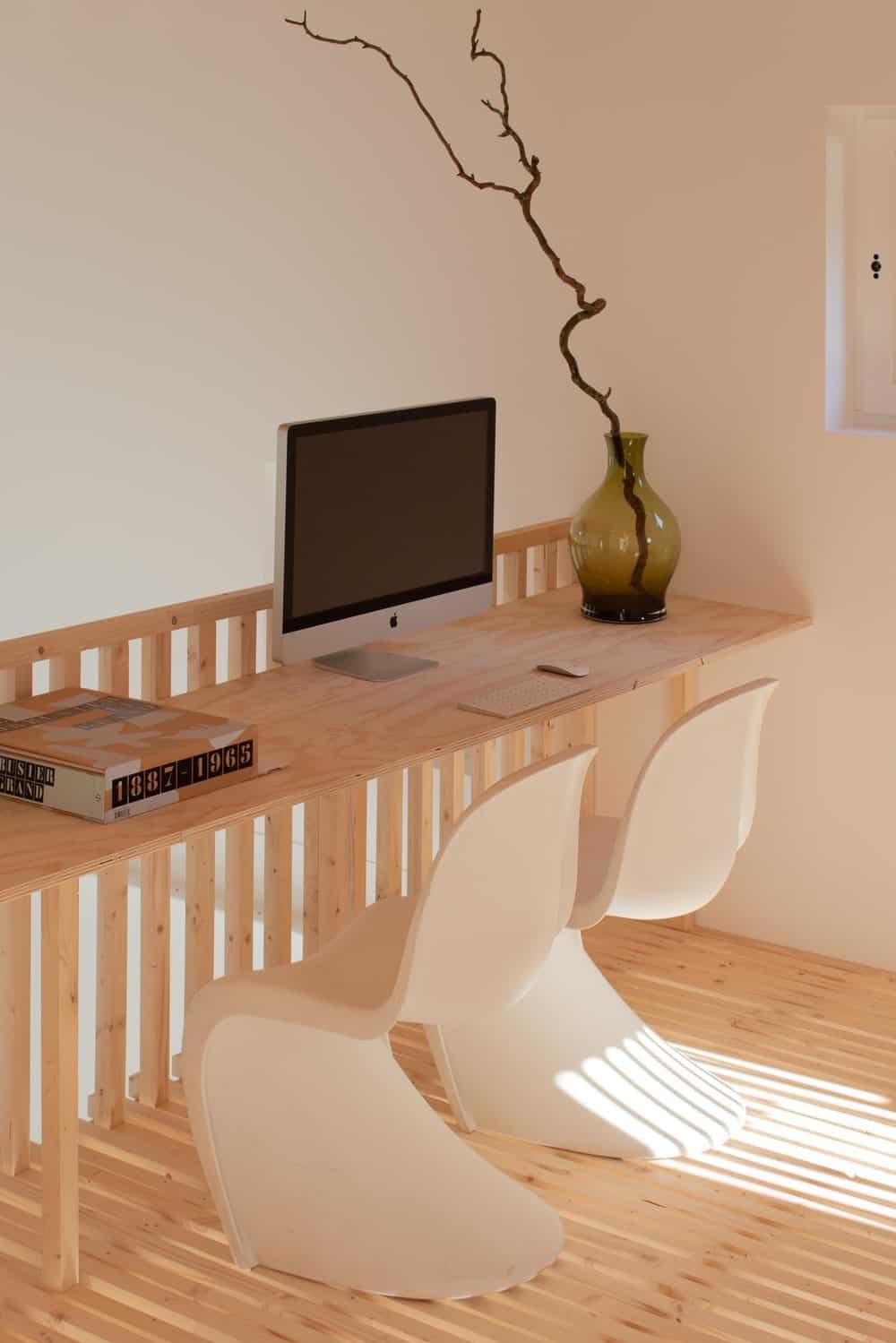 This is a close look at the home office with a wooden built-in desk attached to the wooden railing of the staircase.