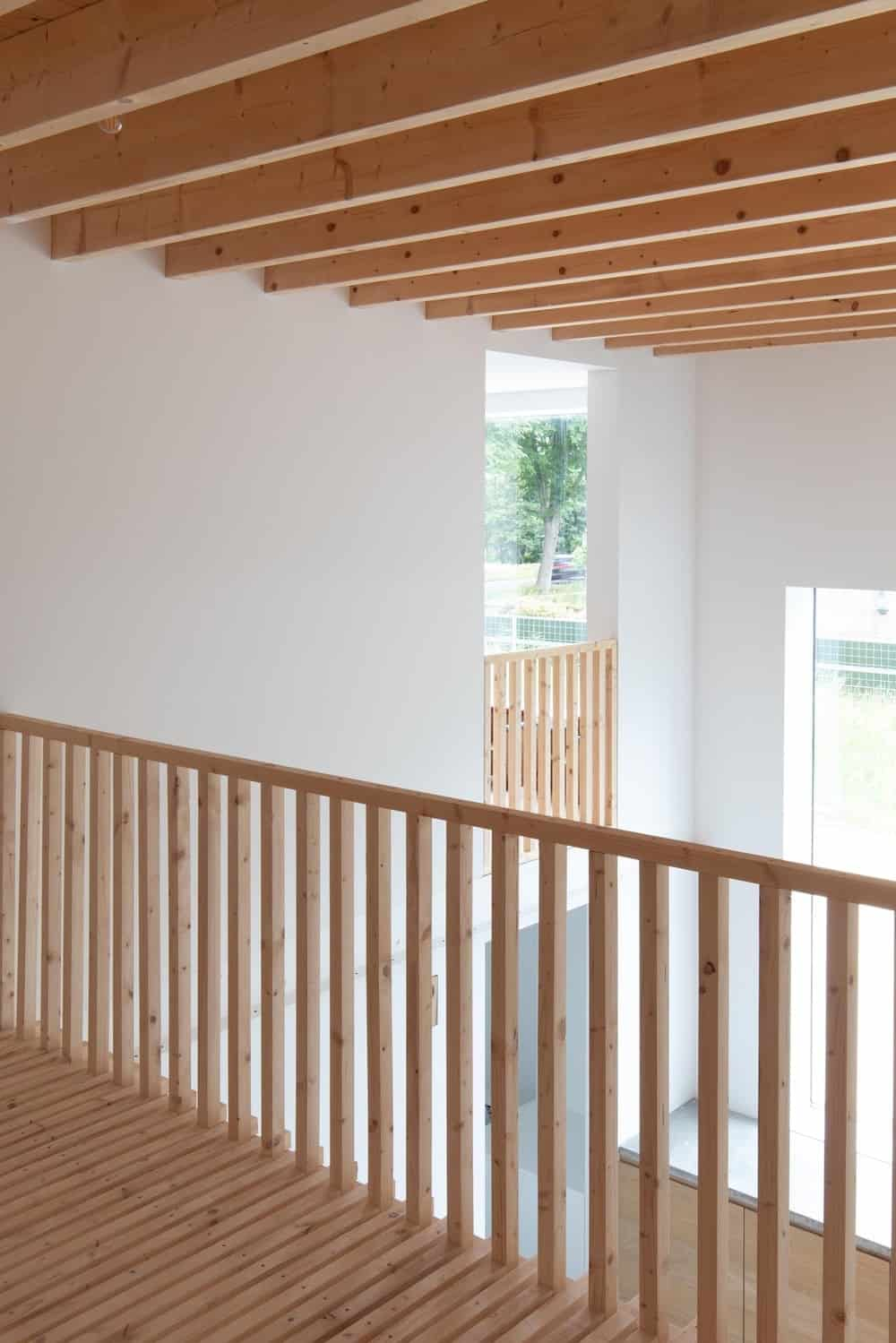 This is the indoor balcony looking over the kitchen with a wooden set of railing that matches with the hardwood flooring and the beamed ceiling.