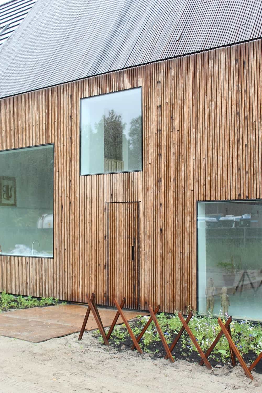 This close look at the front of the house showcases the large glass windows that stand out against the wooden exterior wall.