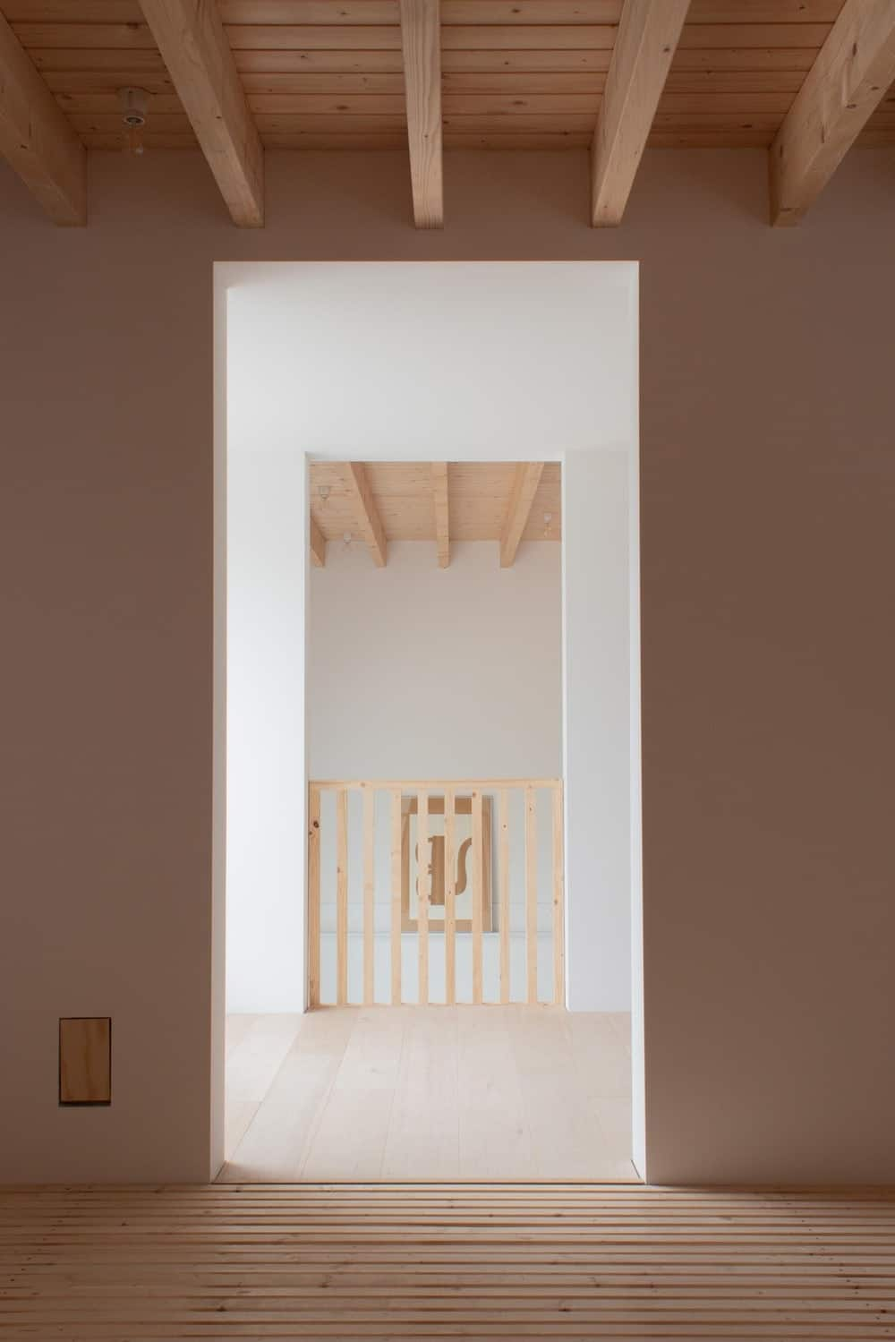 This hallway has tall beige walls and soaring wooden beamed ceiling as seen through archways.