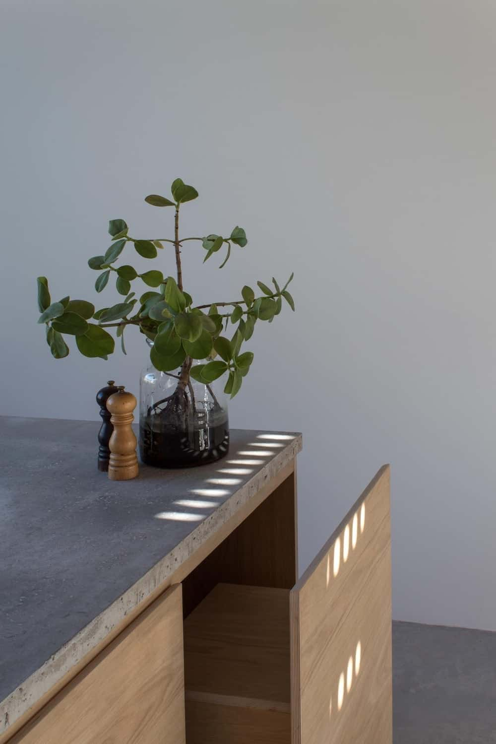 This is a close look at the kitchen island showcasing the wooden chairs that are hidden within its cabinetry.