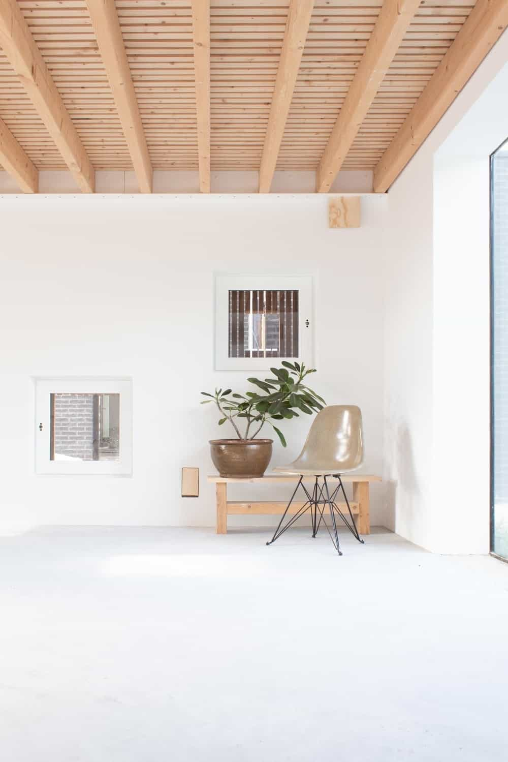 Upon entry of the house, you are welcomed by this simple foyer with a chair, a wooden bench and a potted plant that stands out against the bright elements of the walls and floor.