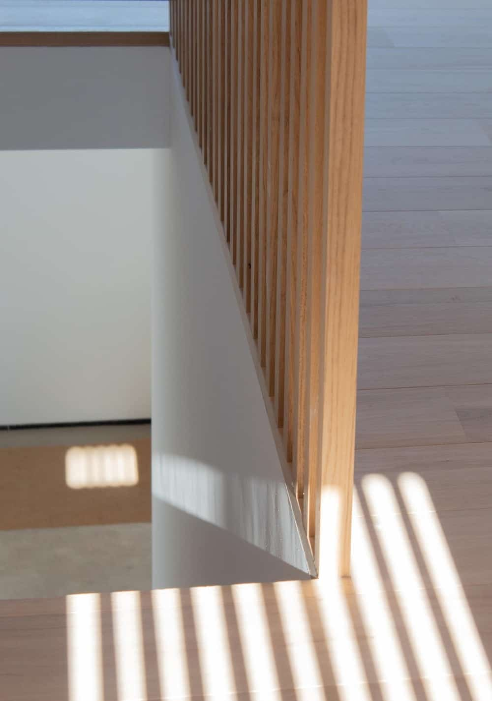 This is a close look at the wooden railing and wall of the staircase that matches with the hardwood flooring.