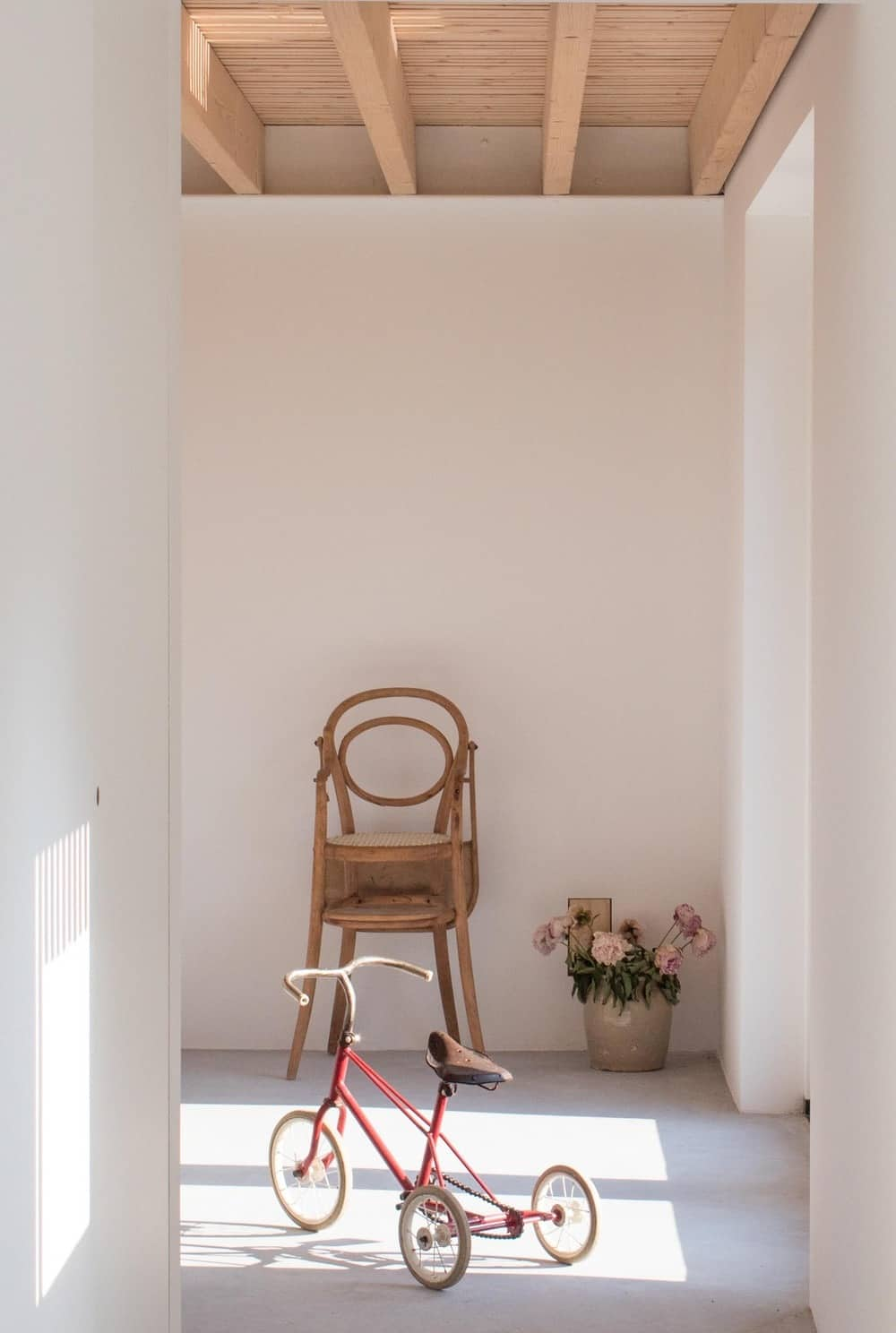 This corner of the house is adorned with a wooden chair, potted plant and a vintage kid's tricycle.