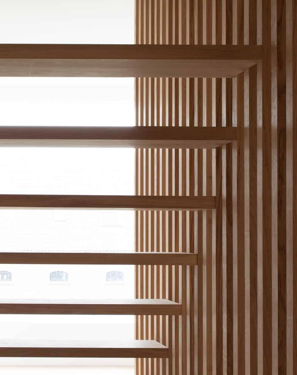 This is the other side of the white wall with a wooden slat wall that is see through and matches the tone of the steps.