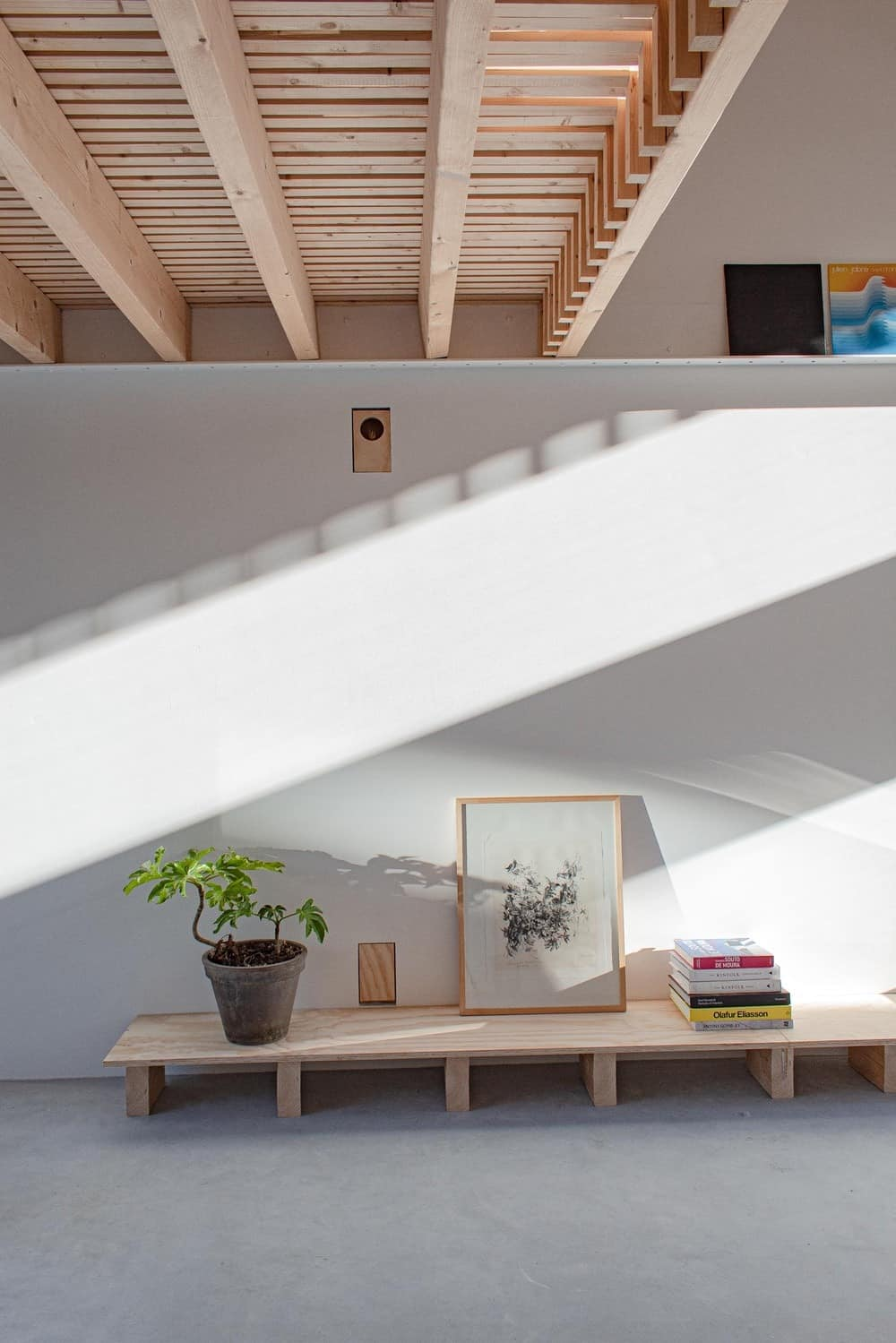 This wall is adorned with a long and low wooden platform that bears a potted plant, a framed artwork and a stack of books for decorative purposes.