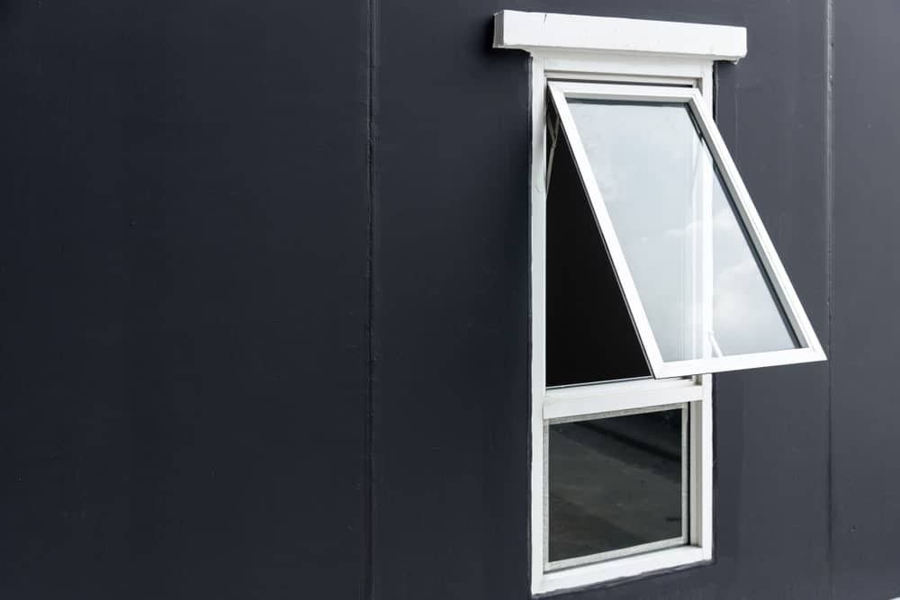 This is a close look at a house with dark exterior walls that make the white casement window stand out.