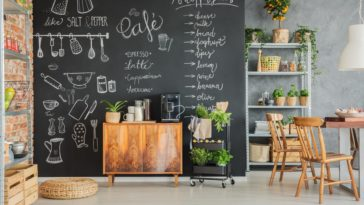A dining area on the side of the kitchen pantry that has a chalkboard wall.