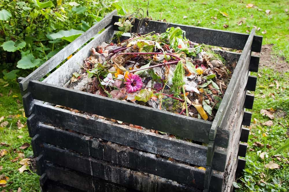 A wooden crate used as a composting bin.