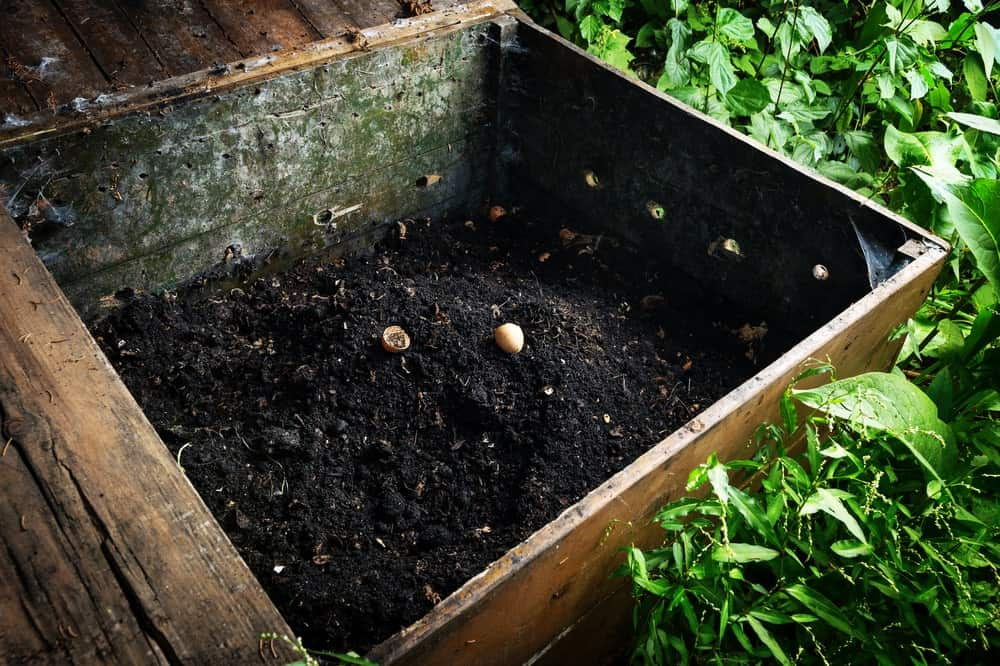 A wooden compost bin with ready to use soil.