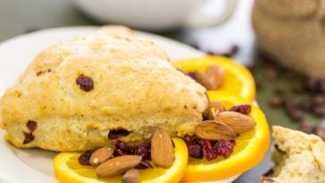 A look at a cranberry orange scone on a plate garnished with orange slices and nuts.
