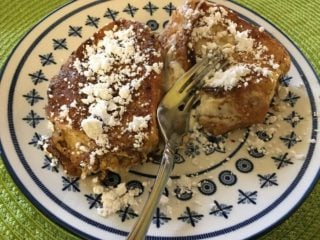 A plate of cream cheese stuffed French Toast with sugar toppings.