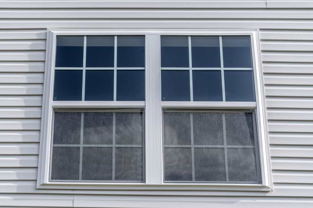 This is a close look at a house with double hung windows that are side by side.