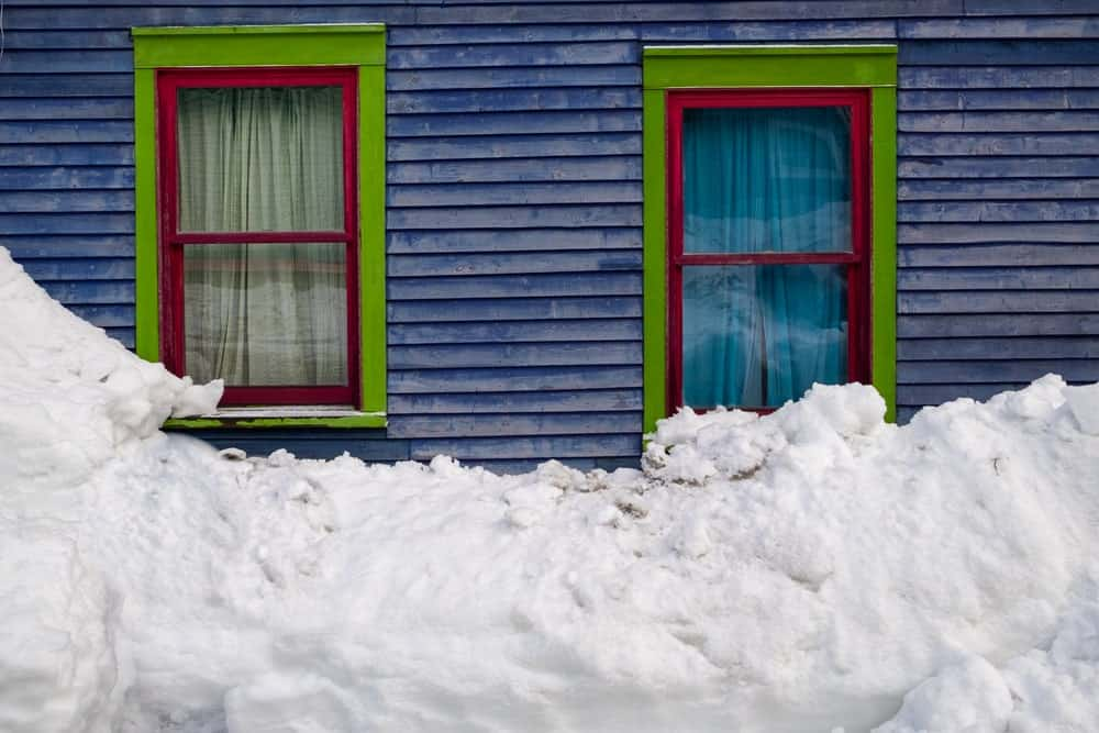 A pair of colorful double hung windows contrasted by the bright snow outside.