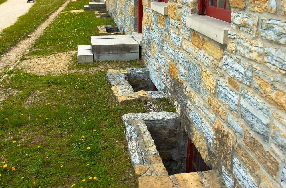 A close look at a stone house with Casement egress windows.